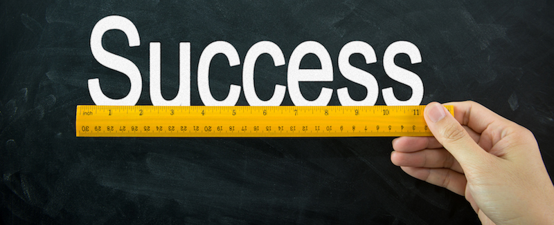 Yellow wooden ruler measures the word success on blackboard