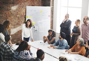 Group of people in a meeting near a whiteboard